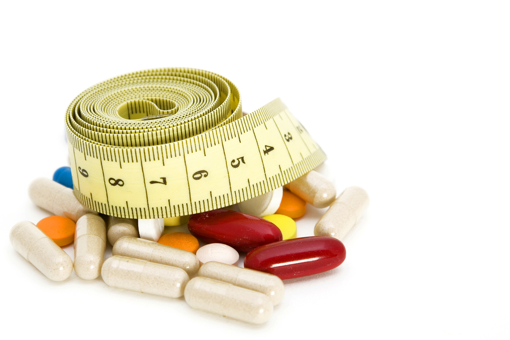 Weight loss concept with a waist-tape and supplements